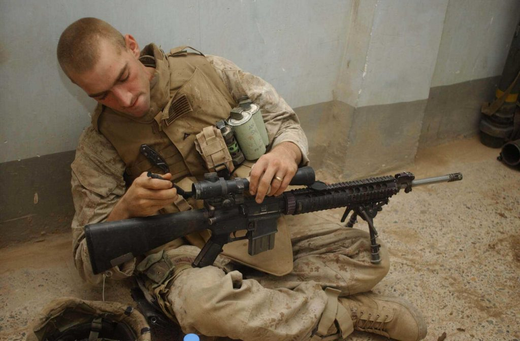 A marine using Lens Pen to clean rifle Scope